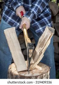 Man splitting log on chopping block with axe