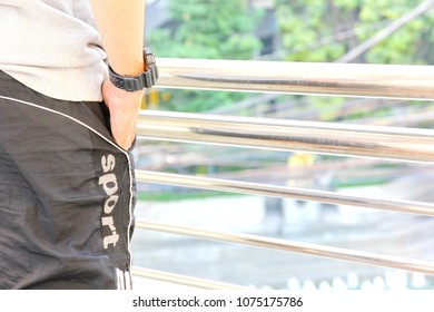 man in sport wear is standing on overpass after joging in in the city