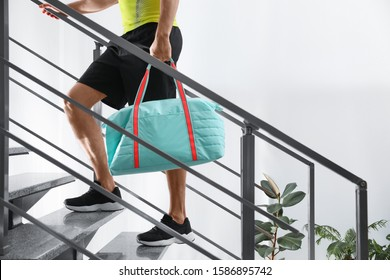 Man with sports bag on stairs indoors, closeup