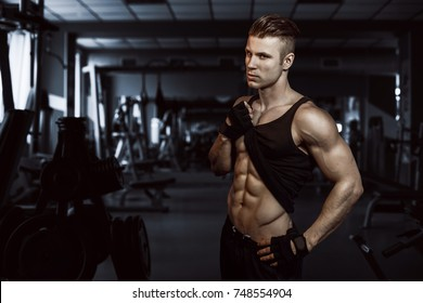 man sports in the gym.Guy in the gym doing the exercise.bodybuilder guy.Muscular man working out in gym. muscular man in gym working out, shaped abdominal.Strong man.