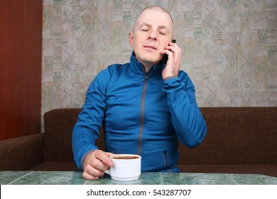 man in a sports jacket, talking on the phone and drinking coffee