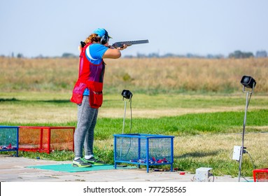 Man sportsman shoots from a double-barreled shotgun, A sports field for a shooting test is shooting at flying skeet and moving targets