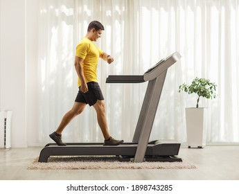 Man in sportswear exercising on a treadmill and looking at his smartwatch at home