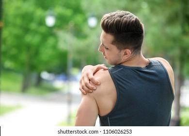 Man in sportswear suffering from shoulder pain outdoors