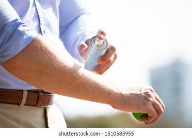 Man Spraying Anti Insect Deet Spray On Skin Over His Arm Outdoors