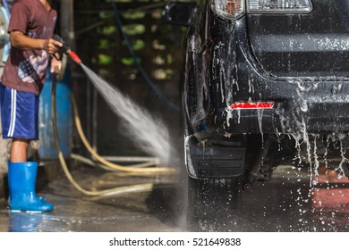 A man spraying pressure washer for car wash in car care shop. Focus on car