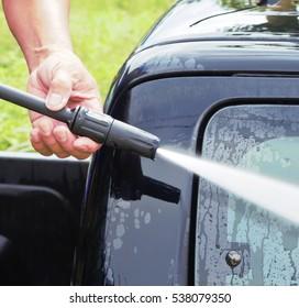 A man spraying pressure washer for car wash