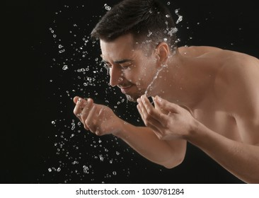Man spraying water on his face after shaving on black background