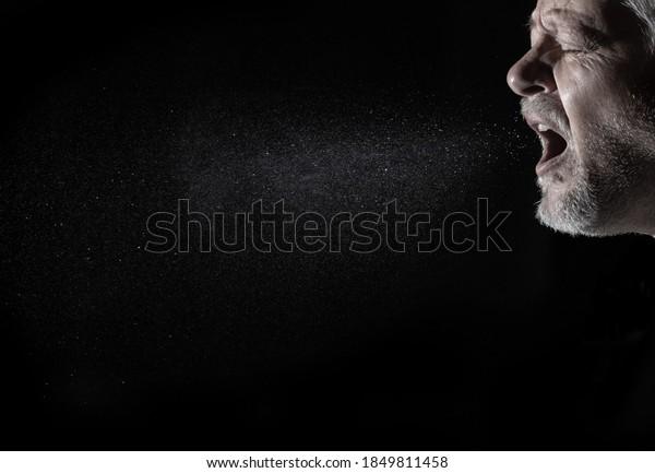 Un hombre rocía aerosoles en el aire mientras hablaba. El fondo es negro.