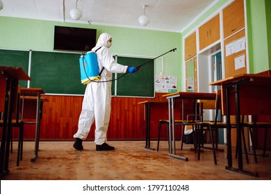 Man sprays disinfection liquid over the desks at the classroom before the school season. Sanitary worker wearing protective suit cleans the auditorium. Students and pupils health care concept.