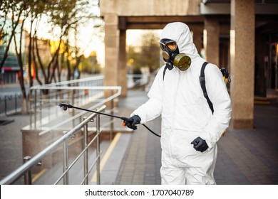 Man sprays disinfector onto the railing wearing coronavirus protective suit and equipment. Cleaning and sterilizing the not crowded city streets. Covid-19 nCov2019 spread prevention