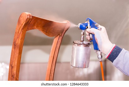 A man sprays with paint paints furniture wooden chair in the furniture industry. Closeup of spray bottle in hand.
