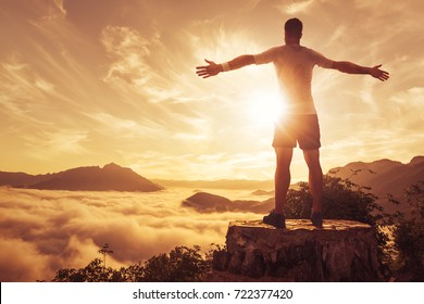 Man with spread arms above the clouds