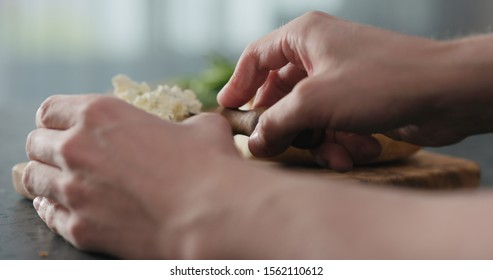 man spread cream cheese on ciabatta slice on olive board