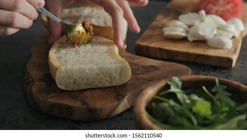 man spread red pesto on ciabatta slice on olive board