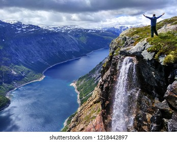 Man spreading arms over the lake Ringedalsvatnet on the way to Trolltunga, Norway.