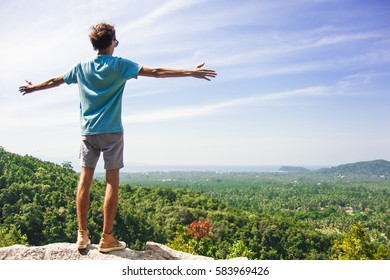 Man with spreading arms is standing on the top of mountain watching amazing landscape
