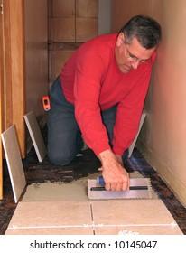Man spreading mortar to install ceramic tiles