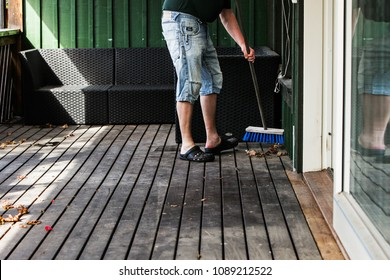 A man is spring cleaning by sweeping a wooden porch with a broom to remove old autumn leaves and prepare for summer.