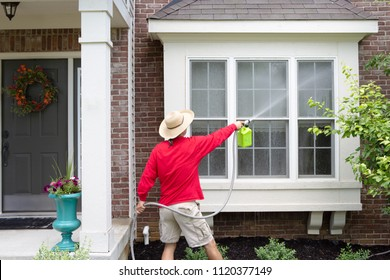 Man spring cleaning the exterior of his house washing down a bay window with a high pressure sprayer attached to a hose pipe in a close up rear view