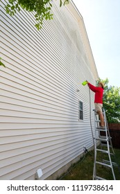 Man spring cleaning the sides of a house using a high pressure nozzle and hosepipe as he stands on a ladder in a profile view