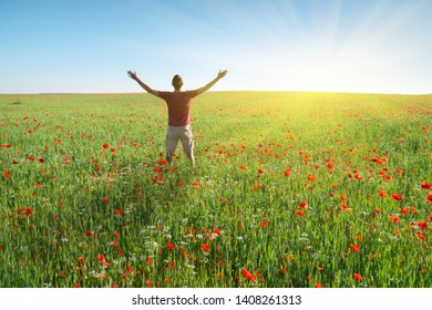 Man in spring meadow of poppy reach to sun. Happy emotional religion and conceptual scene.