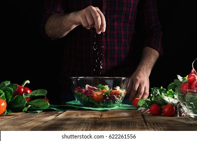 Man sprinkles salt salad of fresh vegetables on a wooden table. Preparing healthy food