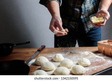 Man is sprinkling the corn grits over the dough balls