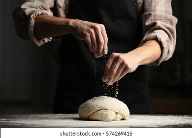 Man sprinkling flour over fresh dough on kitchen table