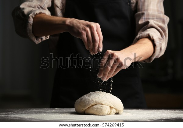 Man sprinkling flour over fresh dough on kitchen table