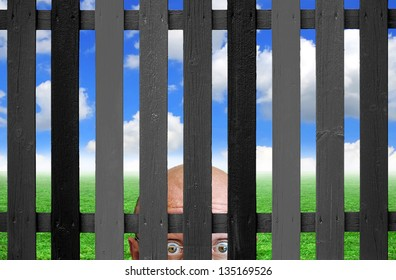 Man spying behind a fence