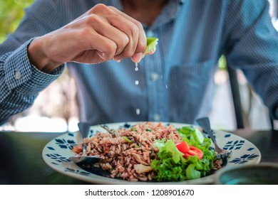 a man squeezing lemons into fried rice with mackerel.
