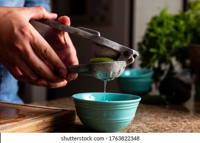 Man squeezing lime with a metal squeezer into a bowl.