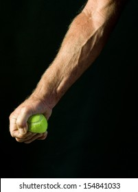 man squeezing tennis ball - study of athlete's forearm muscles and veins
