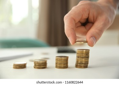 Man stacking coins on table, closeup. Savings concept