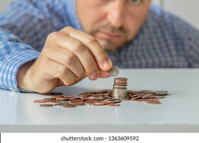 Man stacking coins on table. Frugal behavior.