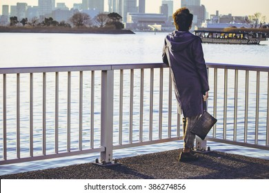 Man stand alone on bridge look to boat in river