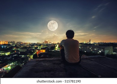 A man stand alone watch the full Moon night in the Bangkok city, Thailand.