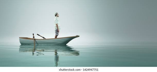 Man stand in a boat at the sea looking to horizon.