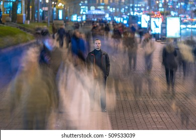 The man stand in crowd flow. Evening night time