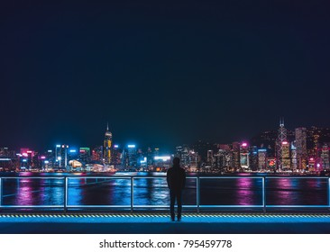A man stand in front of Hong Kong Victoria Harbour.
