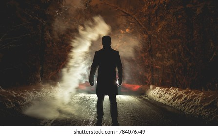 The man stand near the smoke on the snowy road. evening night time
