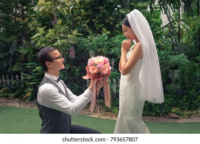 man stand on knee with flower make a proposal to get married to beautiful girlfriend, engagement concept