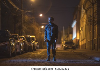 The man stand on the street. Evening night time. Telephoto lens shot