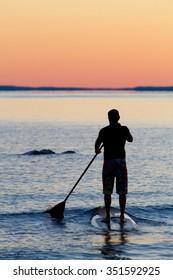 Man stand up paddling at sunset on Georgian Bay