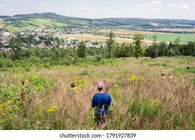 A man standding on a hill and looks at the landscape in summer, a beautiful shot of nature and man hiking