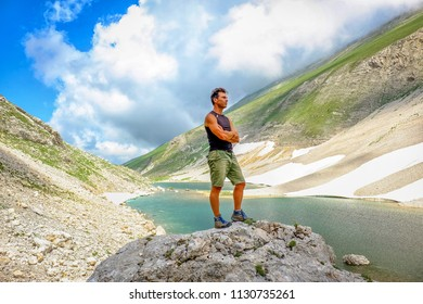 Man standing, after a trekking,  over  big stone in Pilato lake, Sibillini mountains, Marche Italy. Meditation and relaxation concept