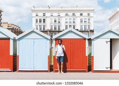 A man standing against the beach huts in Brighton