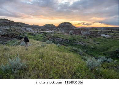 Man standing alone in Canadian badlands looking at sunset