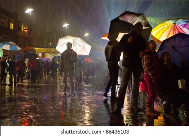 Man standing alone in a crowd when it is raining with enlightened umbrellas.